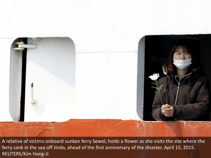 A relative of victims onboard sunken ferry Sewol, holds a flower as she visits the site where the ferry sank in the sea off Jindo, ahead of the first anniversary of the disaster, April 15, 2015. REUTERS/Kim Hong-Ji