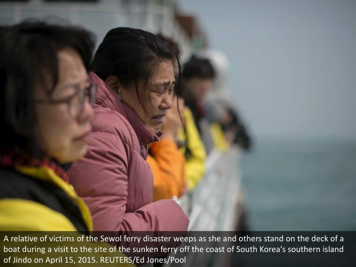 A relative of victims of the Sewol ferry disaster weeps as she and others stand on the deck of a boat during a visit to the site of the sunken ferry off the coast of South Korea's southern island of Jindo on April 15, 2015. REUTERS/Ed Jones/Pool