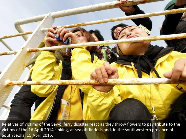 Relatives of victims of the Sewol ferry disaster react as they throw flowers to pay tribute to the v...