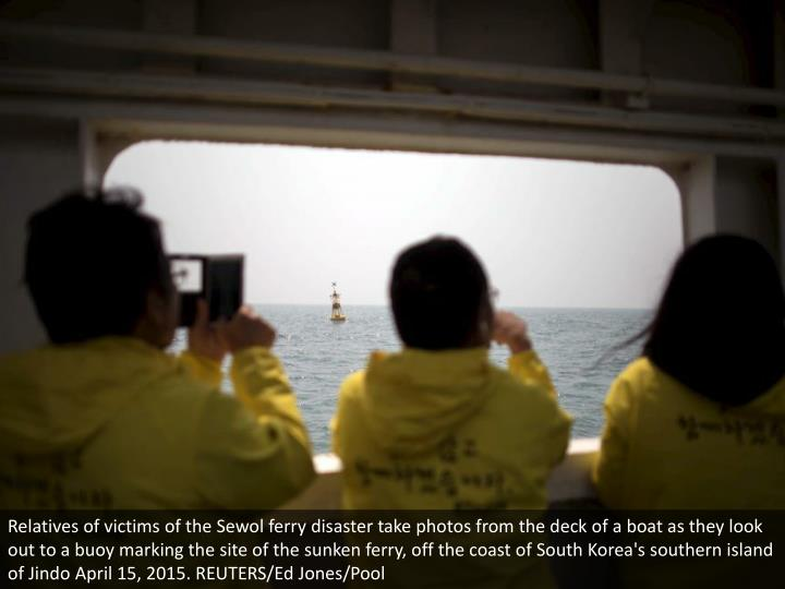 Relatives of victims of the Sewol ferry disaster take photos from the deck of a boat as they look out to a buoy marking the site of the sunken ferry, off the coast of South Korea's southern island of Jindo April 15, 2015. REUTERS/Ed Jones/Pool