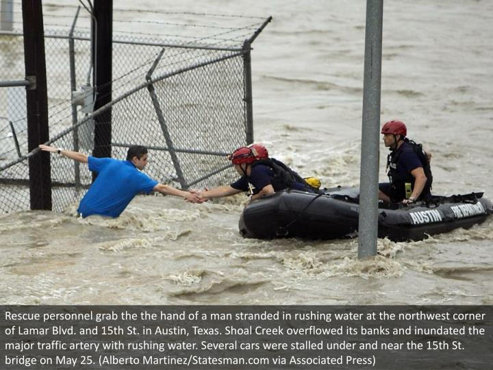 Rescue personnel grab the the hand of a man stranded in rushing water at the northwest corner of Lamar Blvd. and 15th St. in Austin, Texas. Shoal Creek overflowed its banks and inundated the major traffic artery with rushing water. Several cars were stalled under and near the 15th St. bridge on May 25. (Alberto Martinez/Statesman.com via Associated Press)