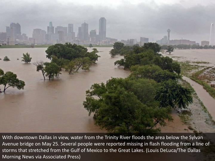 With downtown Dallas in view, water from the Trinity River floods the area below the Sylvan Avenue bridge on May 25. Several people were reported missing in flash flooding from a line of storms that stretched from the Gulf of Mexico to the Great Lakes. (Louis DeLuca/The Dallas Morning News via Associated Press)