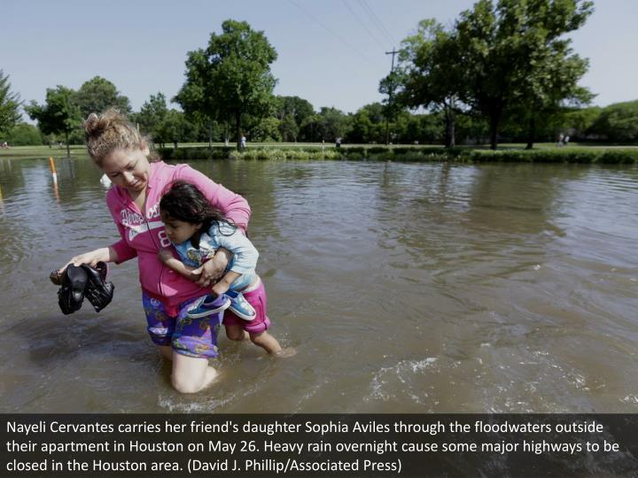 Nayeli Cervantes carries her friend's daughter Sophia Aviles through the floodwaters outside their apartment in Houston on May 26. Heavy rain overnight cause some major highways to be closed in the Houston area. (David J. Phillip/Associated Press)