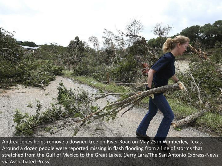 Andrea Jones helps remove a downed tree on River Road on May 25 in Wimberley, Texas. Around a dozen people were reported missing in flash flooding from a line of storms that stretched from the Gulf of Mexico to the Great Lakes. (Jerry Lara/The San Antonio Express-News via Assoctiated Press)