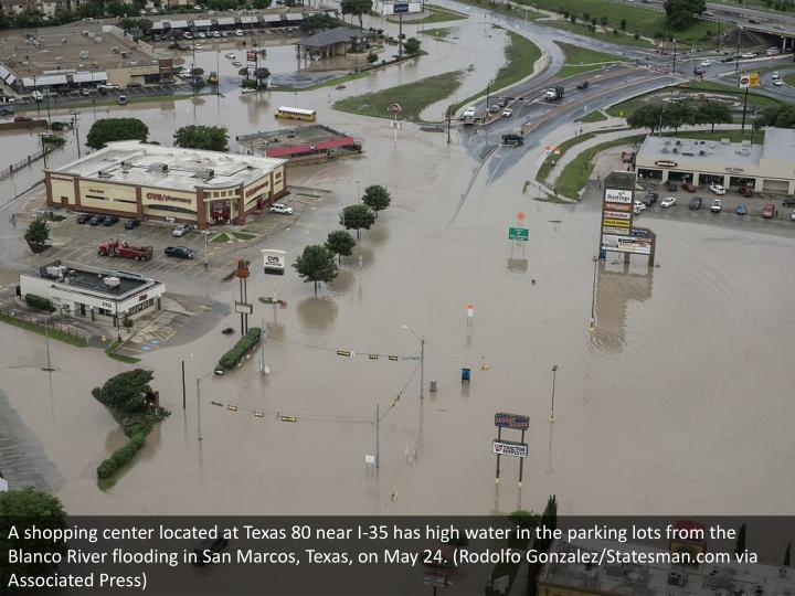 A shopping center located at Texas 80 near I-35 has high water in the parking lots from the Blanco River flooding in San Marcos, Texas, on May 24. (Rodolfo Gonzalez/Statesman.com via Associated Press)