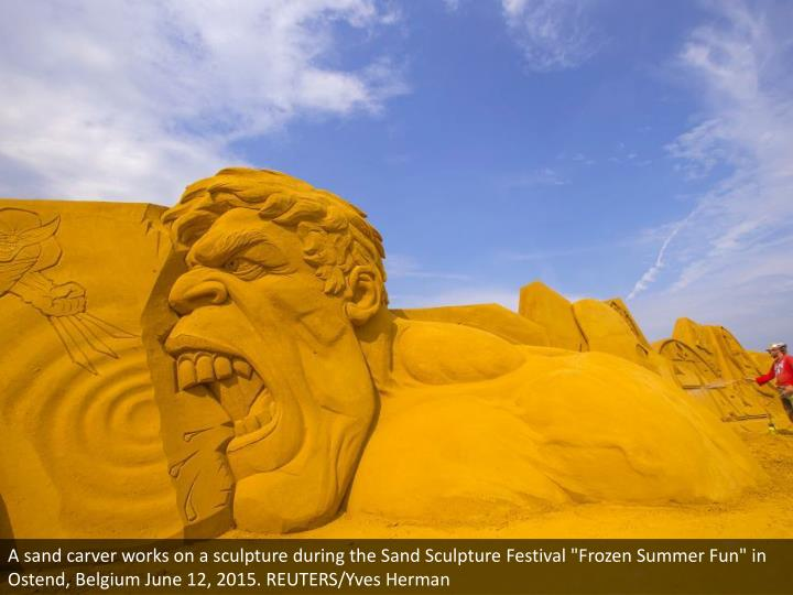 """A sand carver works on a sculpture during the Sand Sculpture Festival """"Frozen Summer Fun"""" in Ostend,..."""