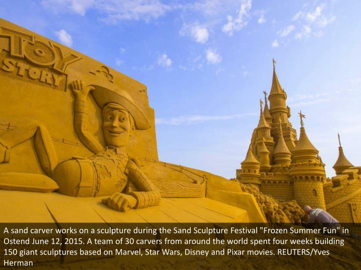 """A sand carver works on a sculpture during the Sand Sculpture Festival """"Frozen Summer Fun"""" in Ostend ..."""