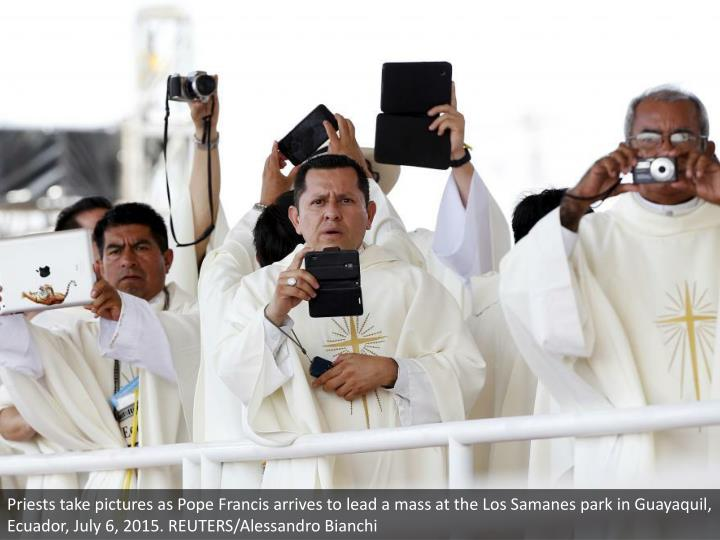 Priests take pictures as Pope Francis arrives to lead a mass at the Los Samanes park in Guayaquil, E...