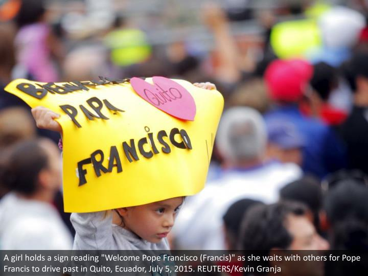 """A girl holds a sign reading """"Welcome Pope Francisco (Francis)"""" as she waits with others for Pope Francis to drive past in Quito, Ecuador, July 5, 2015. REUTERS/Kevin Granja"""