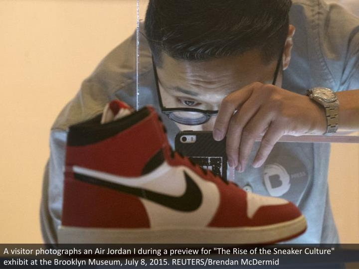 """A visitor photographs an Air Jordan I during a preview for """"The Rise of the Sneaker Culture"""" exhibit..."""
