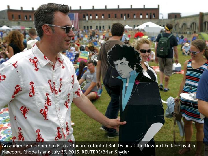 An audience member holds a cardboard cutout of Bob Dylan at the Newport Folk Festival in Newport, Rh...