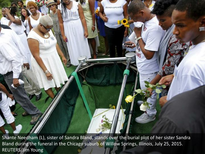 Shante Needham (L), sister of Sandra Bland, stands over the burial plot of her sister Sandra Bland during the funeral in the Chicago suburb of Willow Springs, Illinois, July 25, 2015. REUTERS/Jim Young