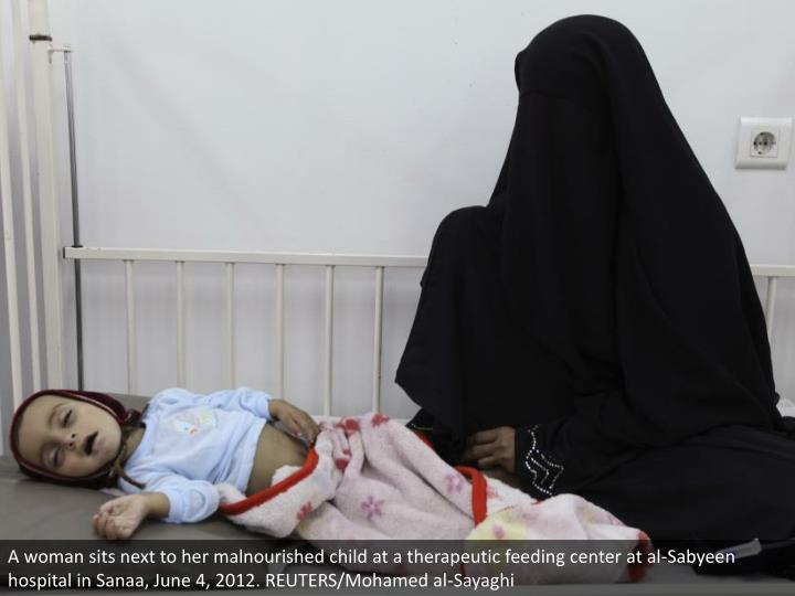 A woman sits next to her malnourished child at a therapeutic feeding center at al-Sabyeen hospital in Sanaa, June 4, 2012. REUTERS/Mohamed al-Sayaghi