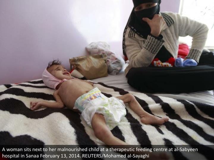 A woman sits next to her malnourished child at a therapeutic feeding centre at al-Sabyeen hospital in Sanaa February 13, 2014. REUTERS/Mohamed al-Sayaghi