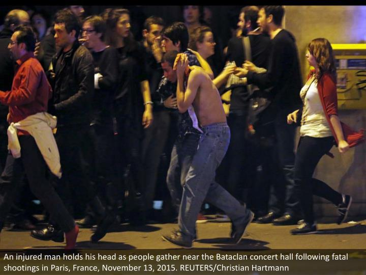 An injured man holds his head as people gather near the Bataclan concert hall following fatal shootings in Paris, France, November 13, 2015. REUTERS/Christian Hartmann