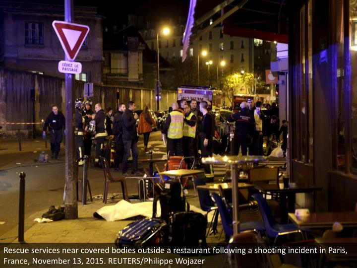Rescue services near covered bodies outside a restaurant following a shooting incident in Paris, France, November 13, 2015. REUTERS/Philippe Wojazer