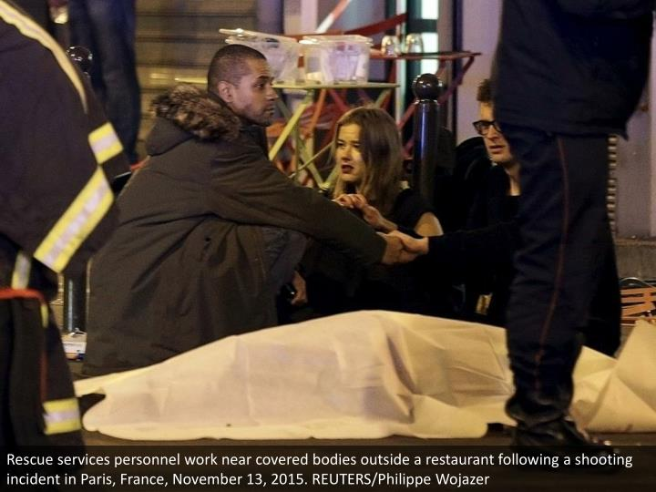 Rescue services personnel work near covered bodies outside a restaurant following a shooting inciden...