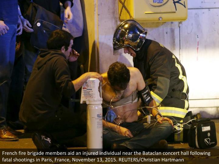 French fire brigade members aid an injured individual near the Bataclan concert hall following fatal shootings in Paris, France, November 13, 2015. REUTERS/Christian Hartmann