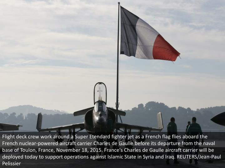 Flight deck crew work around a Super Etendard fighter jet as a French flag flies aboard the French n...