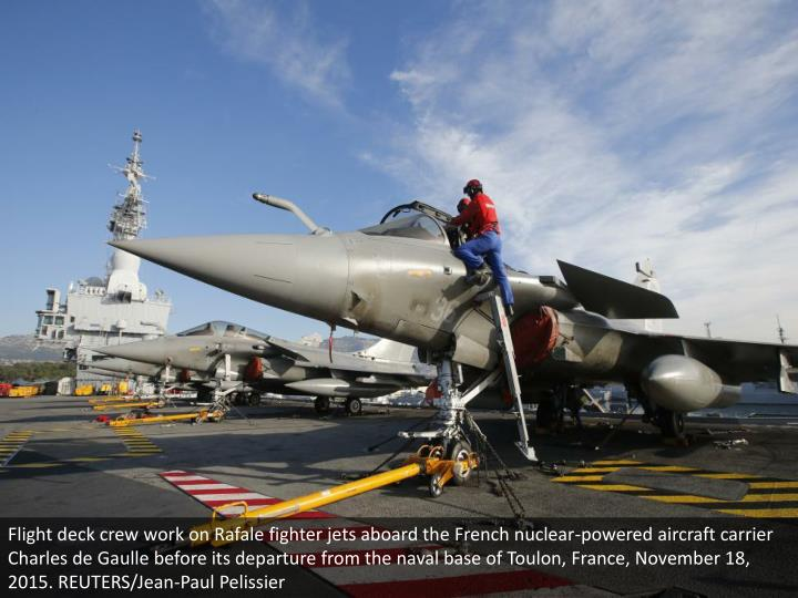 Flight deck crew work on Rafale fighter jets aboard the French nuclear-powered aircraft carrier Charles de Gaulle before its departure from the naval base of Toulon, France, November 18, 2015. REUTERS/Jean-Paul Pelissier