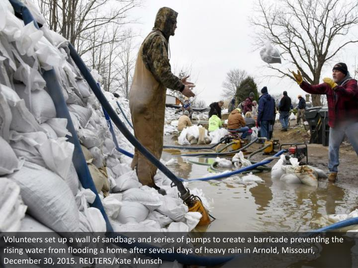 Volunteers set up a wall of sandbags and series of pumps to create a barricade preventing the rising...