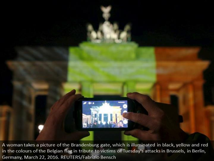A woman takes a picture of the Brandenburg gate, which is illuminated in black, yellow and red in the colours of the Belgian flag in tribute to victims of Tuesday's attacks in Brussels, in Berlin, Germany, March 22, 2016. REUTERS/Fabrizio Bensch