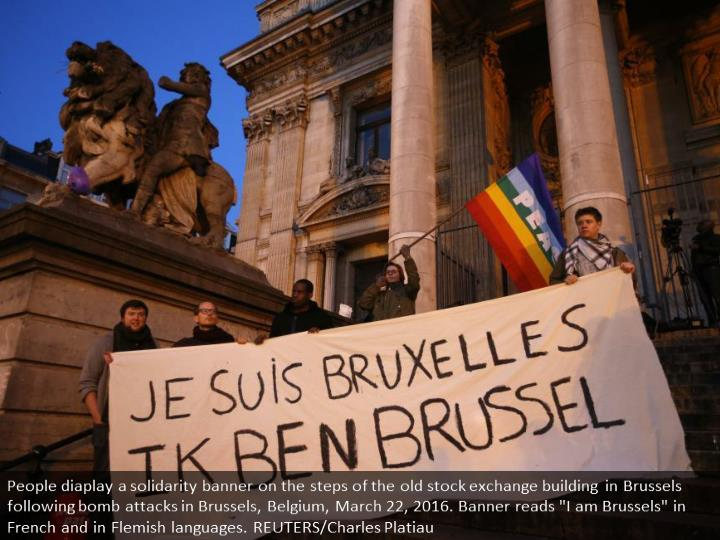 "People diaplay a solidarity banner on the steps of the old stock exchange building in Brussels following bomb attacks in Brussels, Belgium, March 22, 2016. Banner reads ""I am Brussels"" in French and in Flemish languages. REUTERS/Charles Platiau"