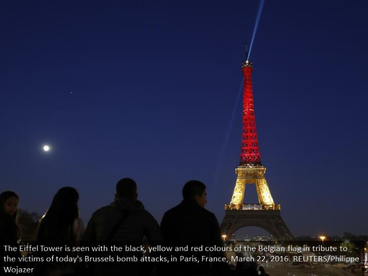 The Eiffel Tower is seen with the black, yellow and red colours of the Belgian flag in tribute to the victims of today's Brussels bomb attacks, in Paris, France, March 22, 2016. REUTERS/Philippe Wojazer