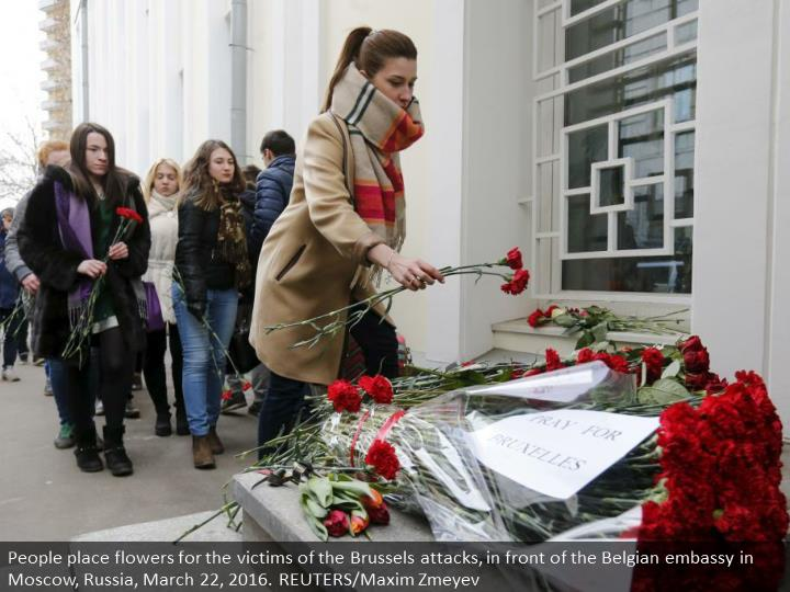 People place flowers for the victims of the Brussels attacks, in front of the Belgian embassy in Moscow, Russia, March 22, 2016. REUTERS/Maxim Zmeyev