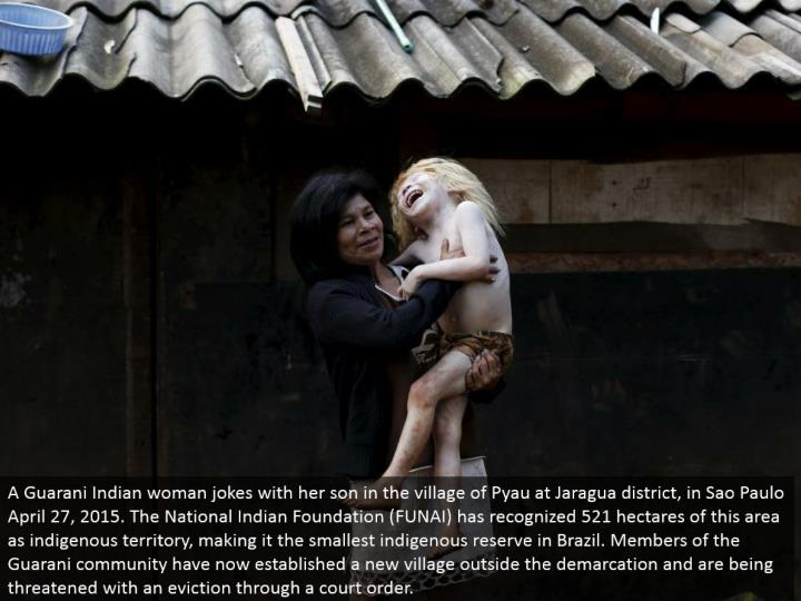 A Guarani Indian lady jokes with her child in the town of Pyau at Jaragua locale, in Sao Paulo April 27, 2015. The National Indian Foundation (FUNAI) has perceived 521 hectares of this zone as indigenous region, making it the littlest indigenous store in Brazil. Individuals from the Guarani people group have now settled another town outside the division and are being debilitated with a removal through a court order.
