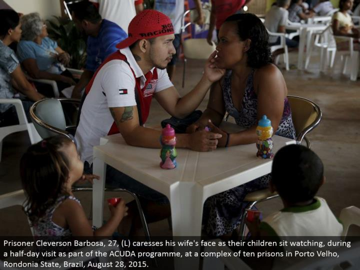 Prisoner Cleverson Barbosa, 27, (L) strokes his better half's face as their kids sit viewing, amid a half-day visit as a major aspect of the ACUDA program, at a complex of ten jails in Porto Velho, Rondonia State, Brazil, August 28, 2015.