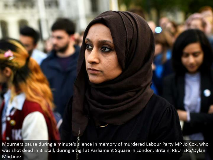 Mourners delay amid a moment's quiet in memory of killed Labor Party MP Jo Cox, who was shot dead in Birstall, amid a vigil at Parliament Square in London, Britain. REUTERS/Dylan Martinez