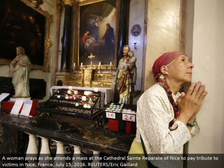 A lady implores as she goes to a mass at the Cathedral Sainte Reparate of Nice to pay tribute to cas...