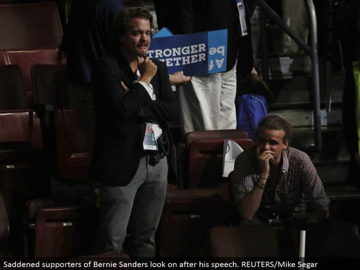 Saddened supporters of Bernie Sanders look on after his discourse. REUTERS/Mike Segar