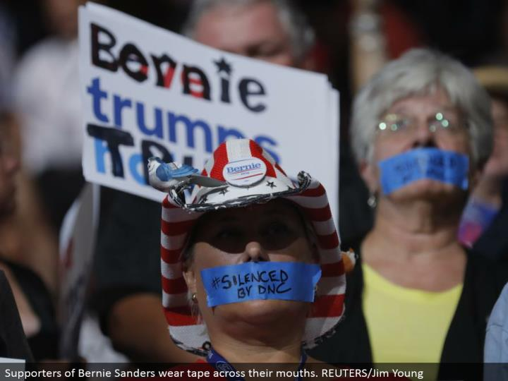 Supporters of Bernie Sanders wear tape over their mouths. REUTERS/Jim Young