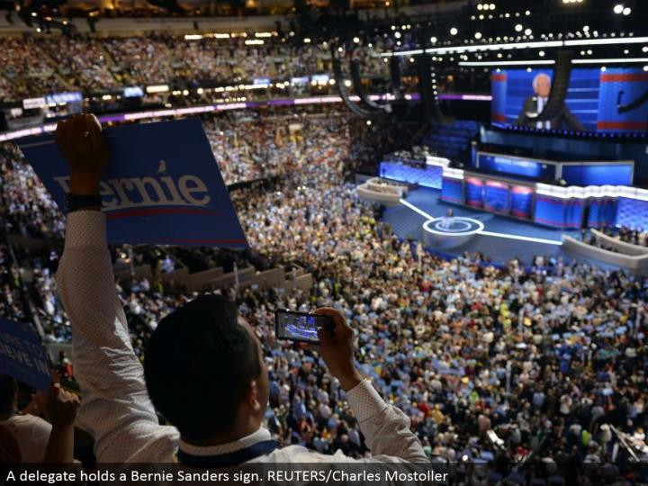 A delegate holds a Bernie Sanders sign. REUTERS/Charles Mostoller