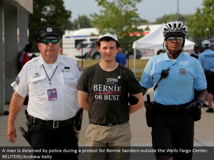 A man is kept by police amid a challenge for Bernie Sanders outside the Wells Fargo Center.  REUTERS/Andrew Kelly