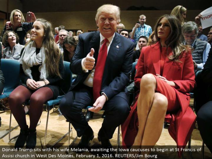 Donald Trump sits with his better half Melania, anticipating the Iowa councils to start at St Francis of Assisi church in West Des Moines, February 1, 2016. REUTERS/Jim Bourg