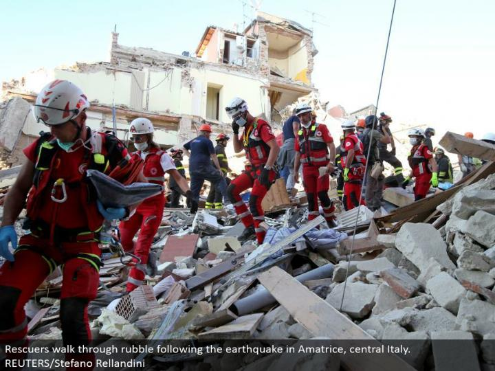 Rescuers walk around rubble taking after the seismic tremor in Amatrice, central Italy. REUTERS/Stefano Rellandini