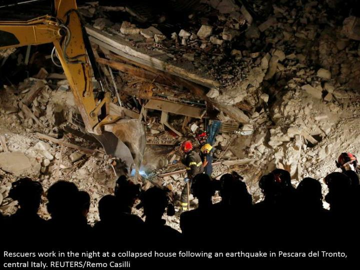 Rescuers work in the night at a given way house taking after a shake in Pescara del Tronto, central ...