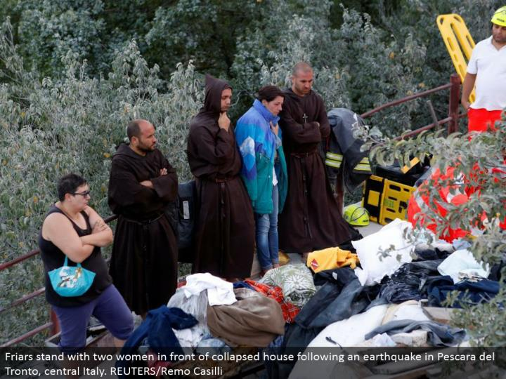 Friars stand with two women before given way house taking after a seismic tremor in Pescara del Tronto, central Italy. REUTERS/Remo Casilli