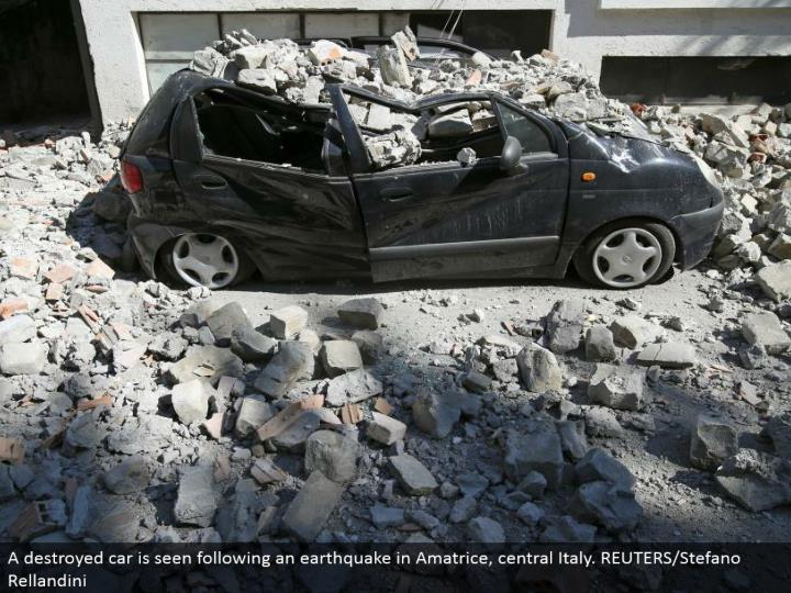 A squashed auto is seen taking after a seismic tremor in Amatrice, central Italy. REUTERS/Stefano Rellandini