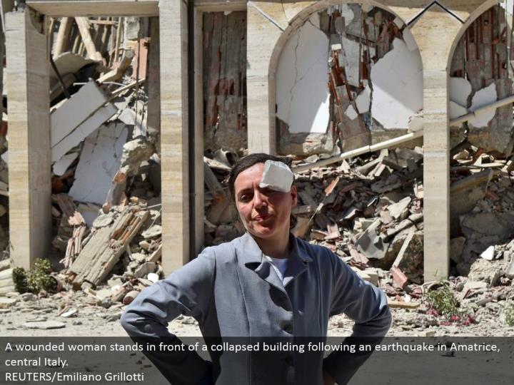 A harmed woman stays before a fallen building taking after a shudder in Amatrice, central Italy.  RE...
