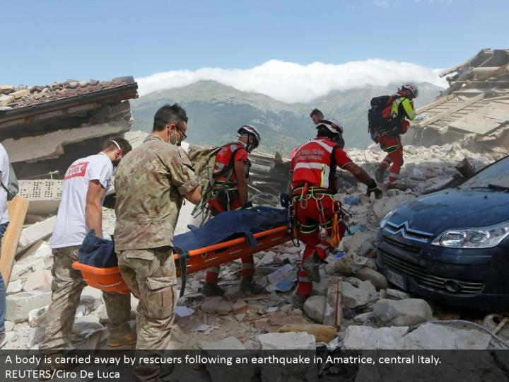 A body is redirected by rescuers taking after a tremor in Amatrice, central Italy. REUTERS/Ciro De Luca