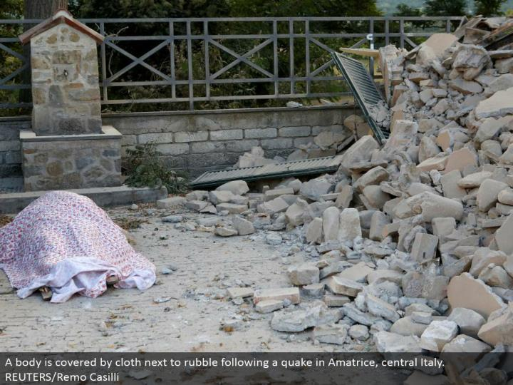 A body is secured by material by rubble taking after a tremor in Amatrice, central Italy. REUTERS/Remo Casilli