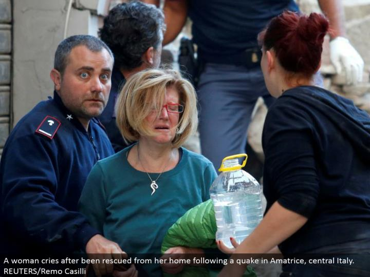A woman cries after been spared from her home after a shake in Amatrice, central Italy. REUTERS/Remo Casilli