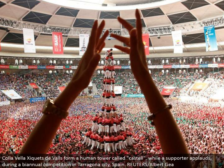 """Colla Vella Xiquets de Valls structure a human tower called """"castell"""", while a supporter commends, amid a semiannual rivalry in Tarragona city, Spain. REUTERS/Albert Gea"""