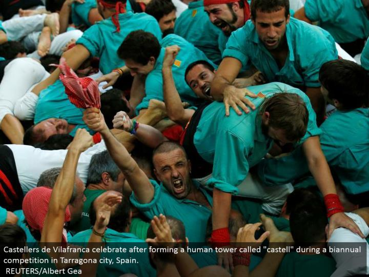 """Castellers de Vilafranca celebrate in the wake of framing a human tower called """"castell"""" amid a semiannual rivalry in Tarragona city, Spain.  REUTERS/Albert Gea"""