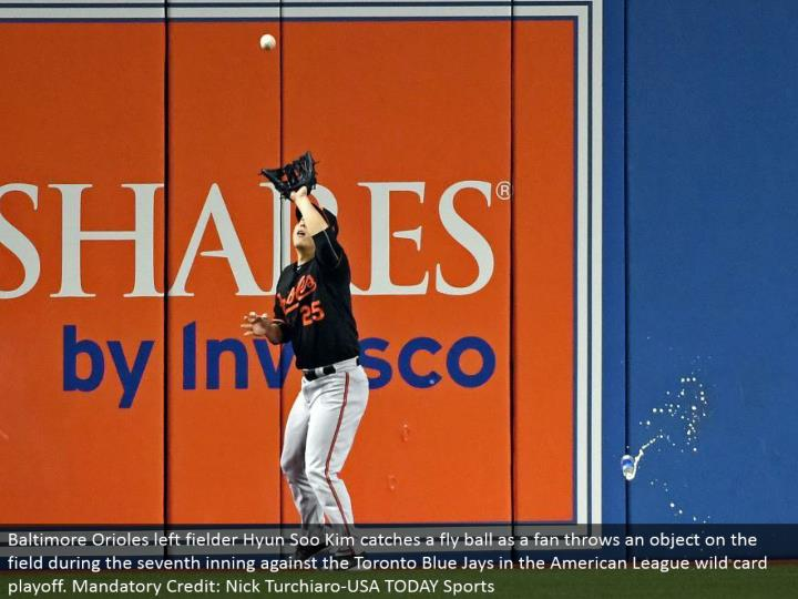 Baltimore Orioles left defender Hyun Soo Kim gets a fly ball as a fan tosses a question on the field amid the seventh inning against the Toronto Blue Jays in the American League special case playoff. Required Credit: Nick Turchiaro-USA TODAY Sports