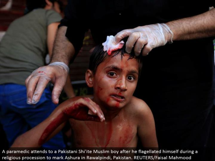 A paramedic takes care of a Pakistani Shi'ite Muslim kid after he flogged himself amid a religious p...